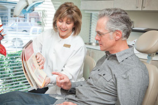 Dental technician showing patient dental diagrams in a book